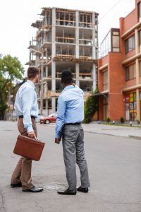African-American businessman and a Caucasian businessman discussing a construction project on the background of building a house