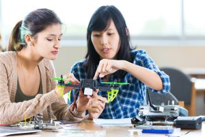 Pretty Asian teacher at STEM school helps Hispanic student with drone in engineering class. The teacher is pointing to something on the drone as the student looks on. The controller and other parts or tools are on the table. The teacher is wearing a blue plaid shirt and the student is wearing trendy layered clothing.